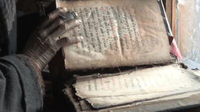 Agafia bladert door een oud gebedenboek