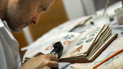 Onderzoeker aan het werk op een facsimile van het manuscript