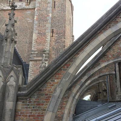 Op het dak tussen de luchtbogen, links de bakstenen torenromp