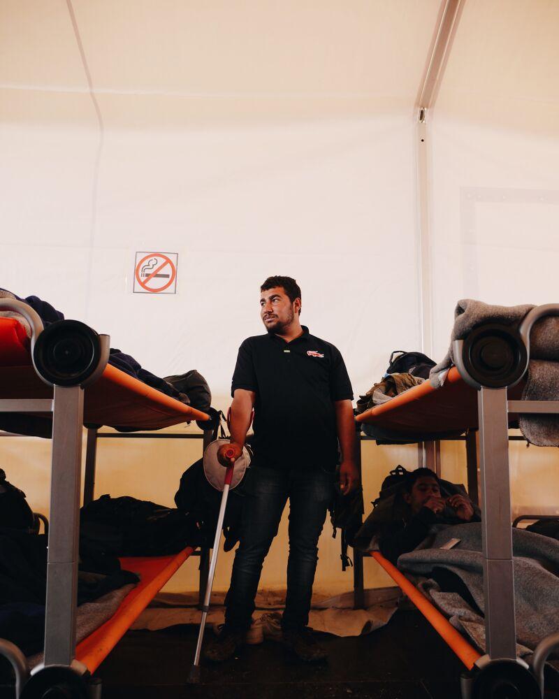 Man met kruk tussen bedden in één van de tenten van UNHCR.