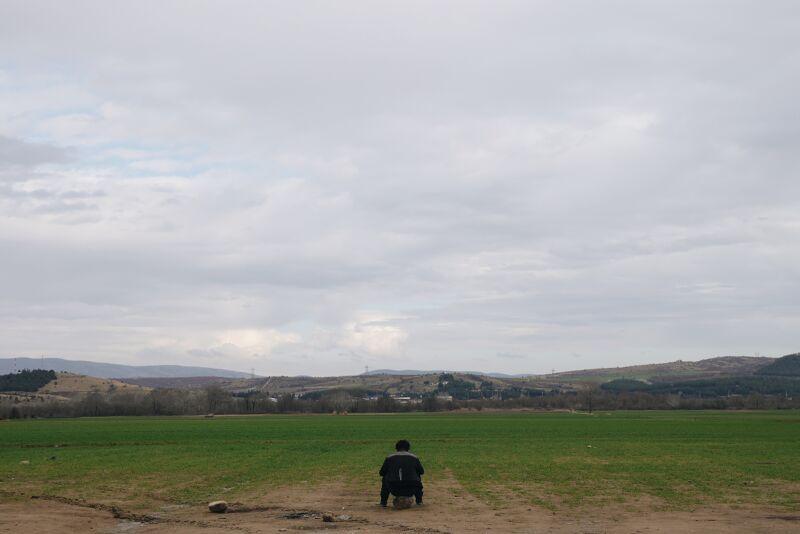 Man in Idomeni zit op een steen en kijkt uit op Macedonië waar hij zo graag naartoe wil