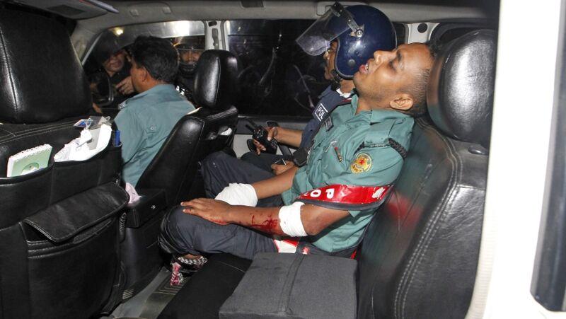 Een gewonde politie-agent wordt weggevoerd na de gijzeling in Bangladesh