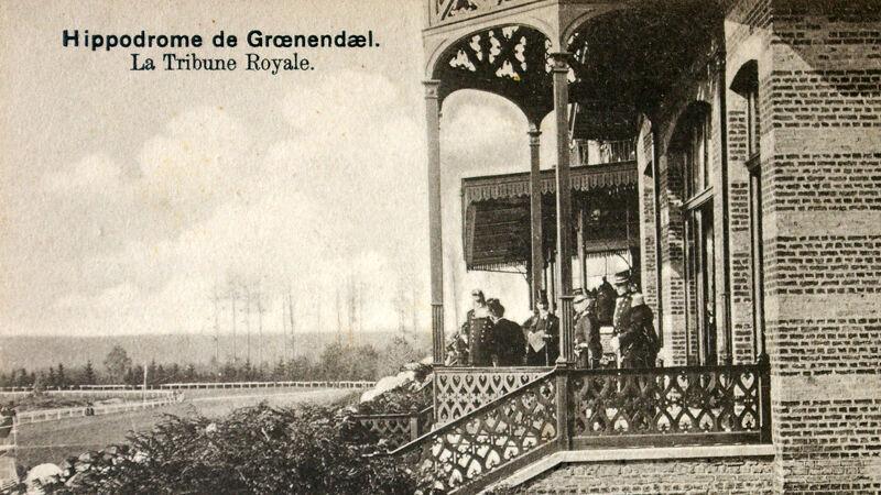 Koninklijke loge: op het terras bemerk je Leopold II en gasten. Aan de slagschaduwen zie je dat ze recht in het zonlicht staan.