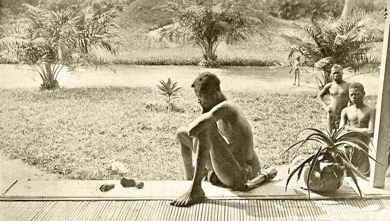 Nsala starend naar de hand en voet van zijn dochter. Foto van Alice Seeley Harris (1904)