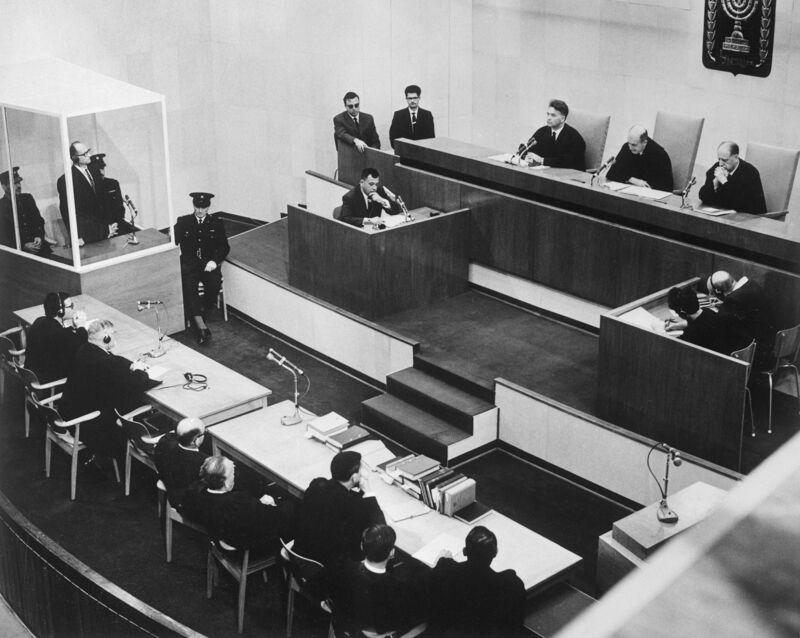 Eichmann in de glazen kooi, links, tijdens zijn proces in Jeruzalem. Hij werd veroordeeld tot de dood door ophanging voor zijn rol in de massamoord op de joden.