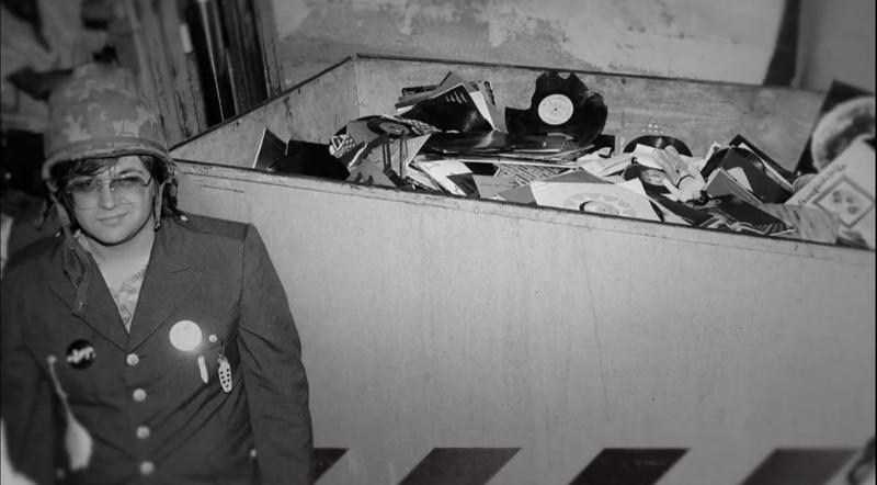 Steve Dahl, voor de gelegenheid als militair verkleed, naast de container met gesneuvelde platen