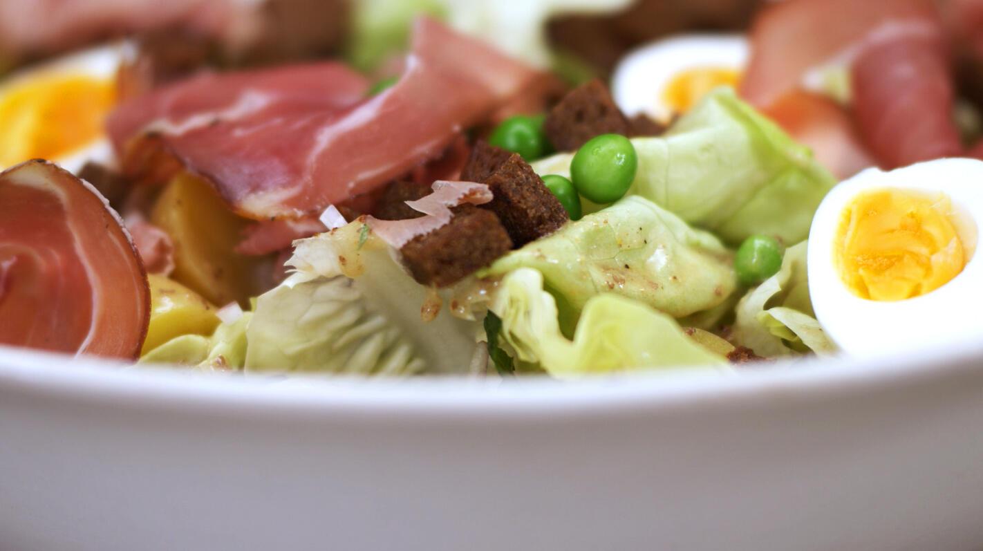 Salade met erwten, rauwe ham en croutons