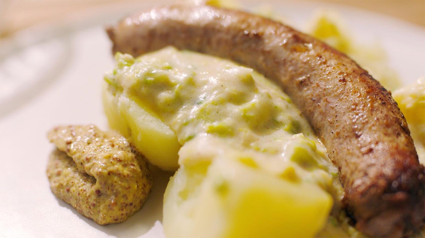 Worst met savooikool, kaassaus en gekookte aardappelen