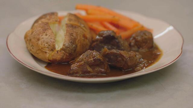 Varkenswangen met oud bruin bier, wortelen en gepofte aardappelen
