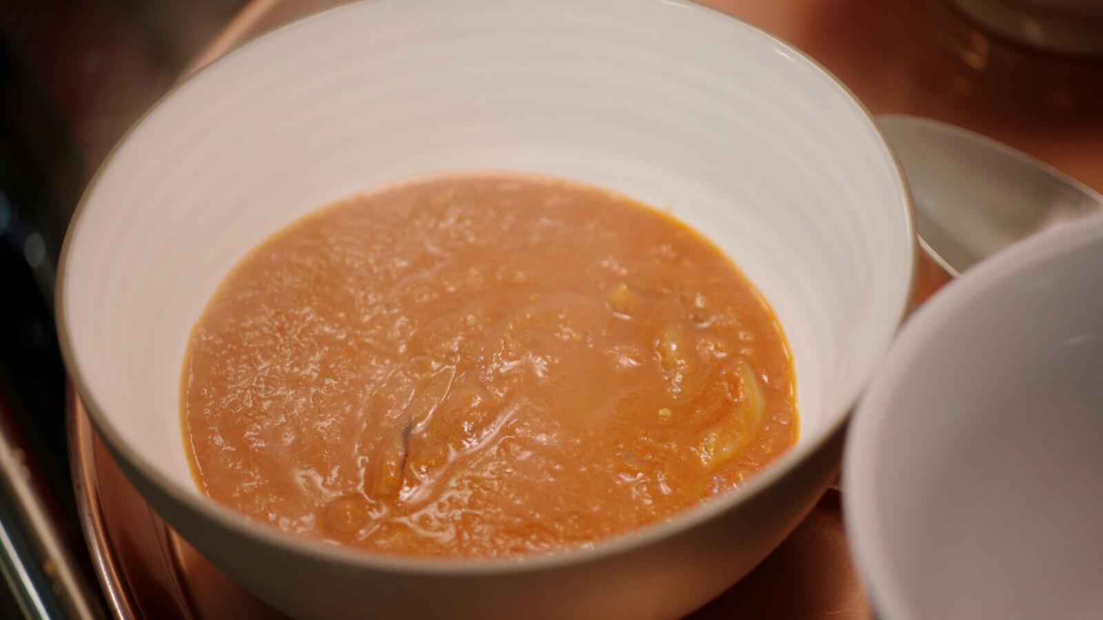 Uien- en tomatensoep met gebakken ui en spekjes