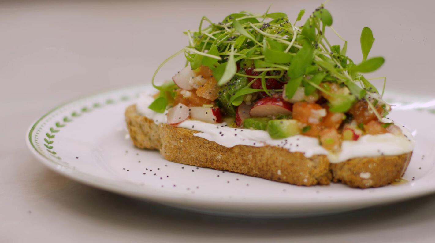 Bruine boterham met plattekaas en salade van radijs