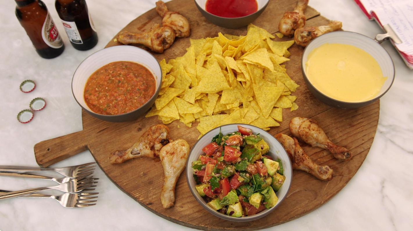 Nacho's met kaasdip, tomatensalsa, drumsticks en sweet chili