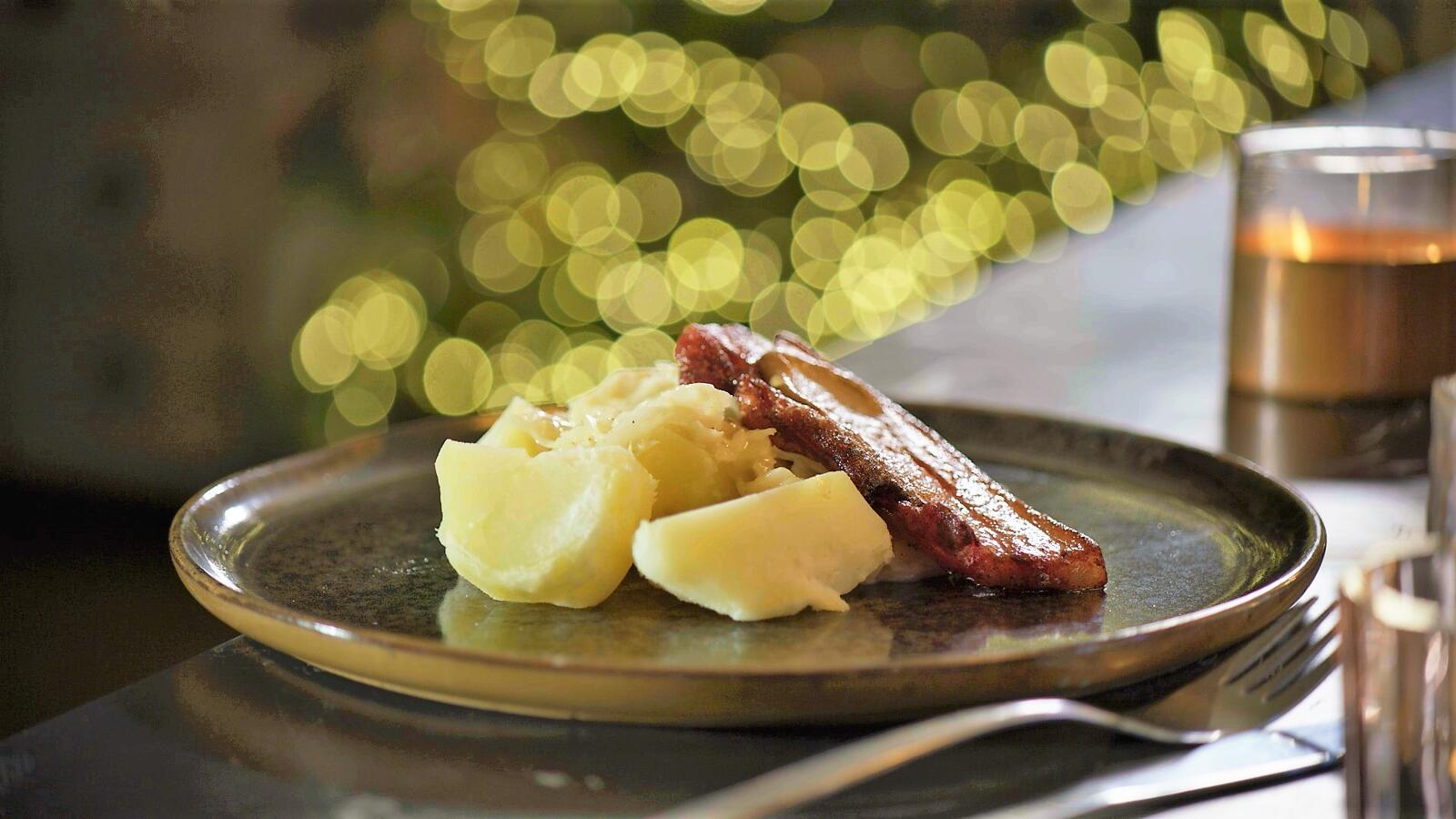 Gebakken spek met witte kool in witte saus en aardappelen