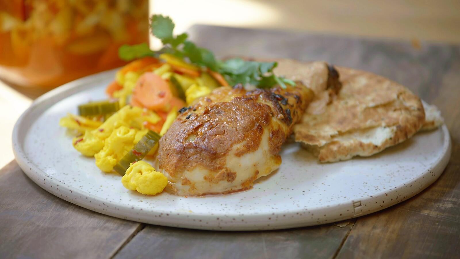 Kip tandoori aan het spit met opgelegde groenten en naan