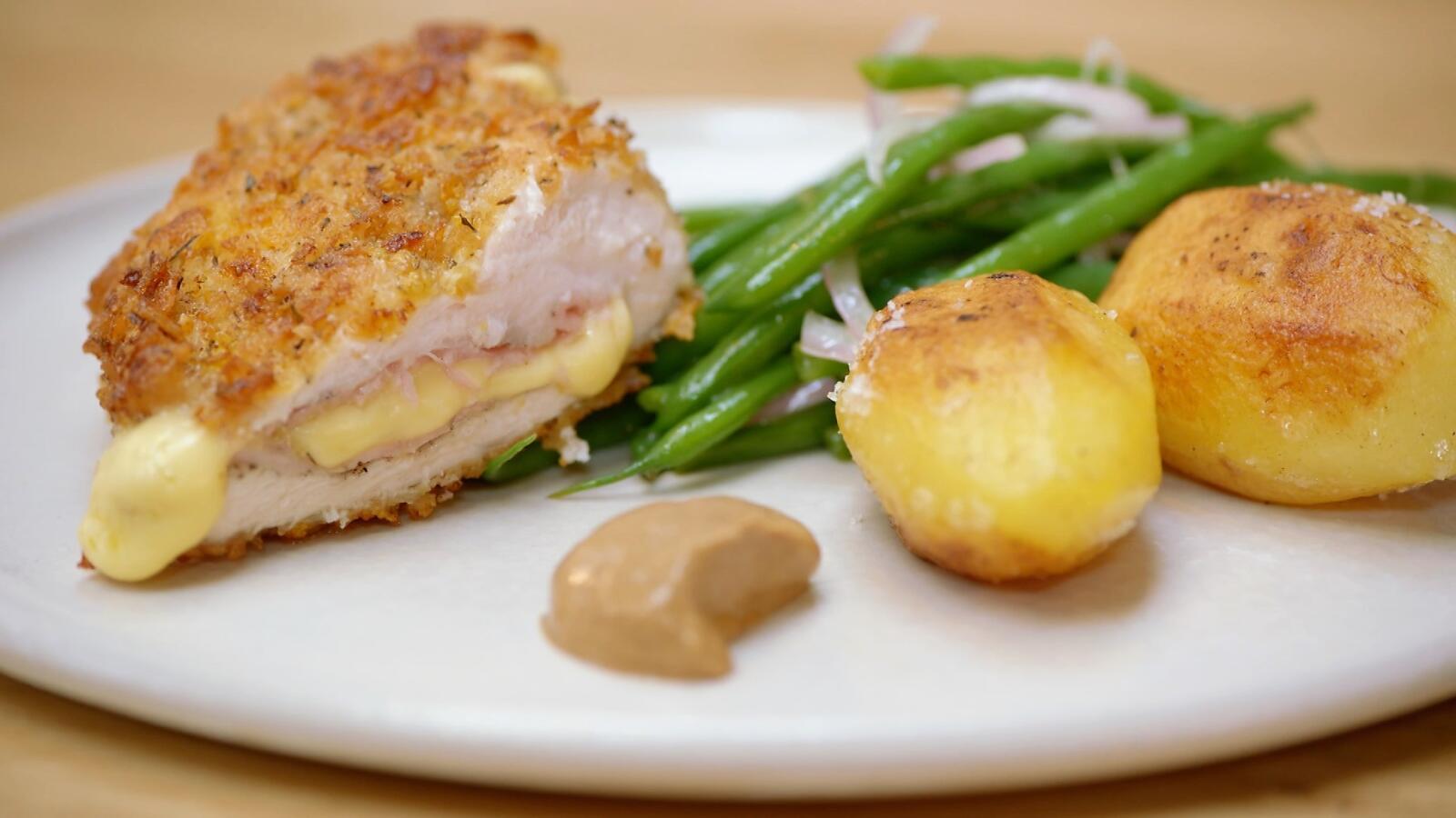 Gepaneerde kip met ham en kaas, gebakken aardappelen en boontjes